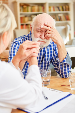 Depressed senior man is comforted by family doctor or geriatric nurse