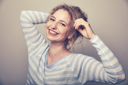Laughing young woman with blond hair looks happy into the camera