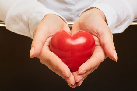 Hands hold red heart as a symbol of care and health precaution Stock Photo