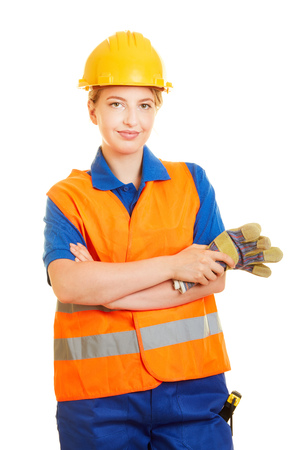 Young woman as a construction worker with helmet and safety vest and protective gloves for occupational safety