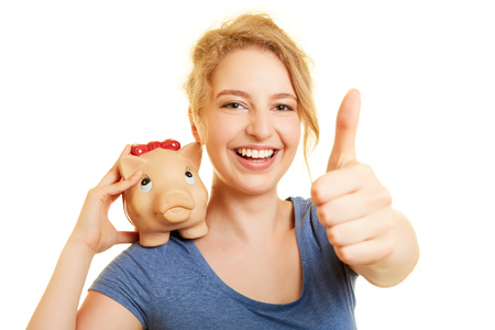 Young woman with piggy bank gives approval to investment with a thumbs up