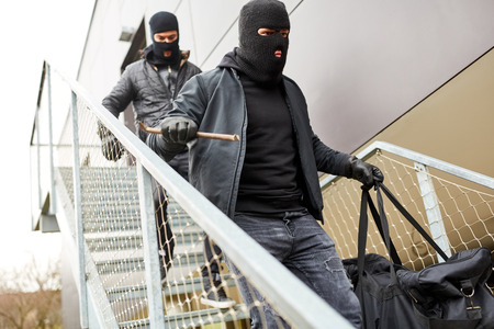 Two hooded burglars flee with booty on stairs