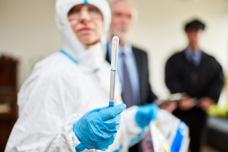 Forensic Technician shows swabs to remove DNA at the scene after a crime Banco de Imagens