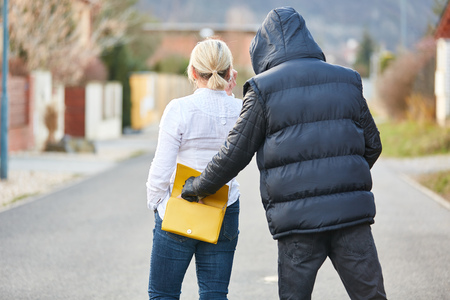 Thief in pickpocketing from handbag on the open road