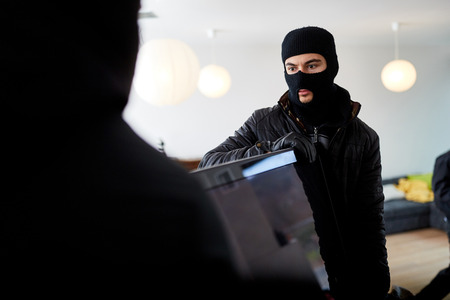 Two burglars steal a big TV from the living room of a house Banco de Imagens