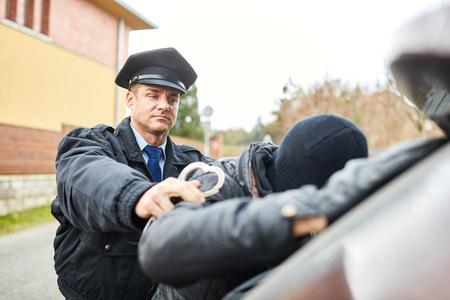 Un policier arrête un cambrioleur avec des menottes