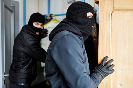 Two burglars look for valuables in a house during a burglary