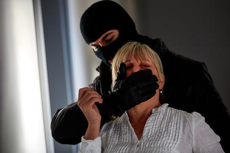 Un voleur à capuchon menace une femme de cambriolage dans la maison Banque d'images