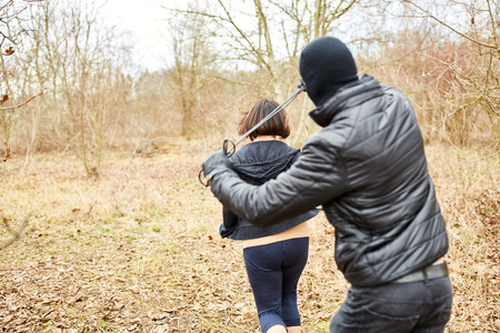 Attacker threatens jogger with robbery in the forest with a noose Stockfoto
