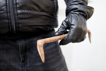 Hand of burglar with crowbar or crowbar