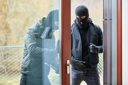 Deux cambrioleurs ouvrent la porte-fenêtre de la maison en entrant par effraction avec un pied de biche