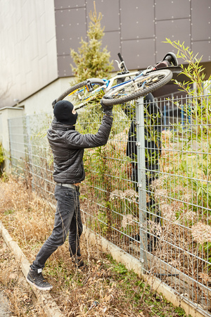 Bicycle thieves lift bike over fence while stealing Banco de Imagens