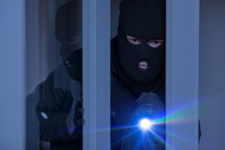 Einbrecher nachts mit Taschenlampe am Fenster des Hauses