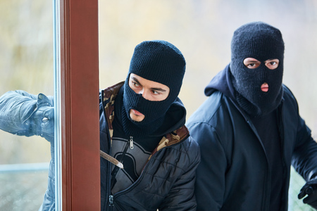 Two burglars open door when breaking into a house