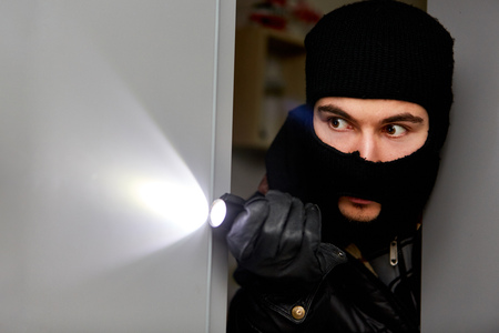 Burglar in the house with flashlight looks for prey in a burglary Banco de Imagens