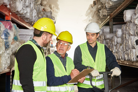Order picker with checklist and clipboard and warehouse worker in shipping
