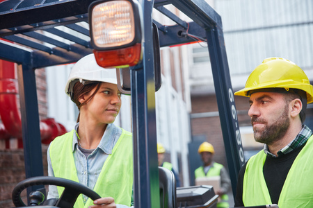 Woman as forklift driver and colleague work together in a freight forwarder