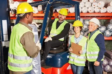 Team warehouse workers with forklift in carpet warehouse prepare a ship Banco de Imagens