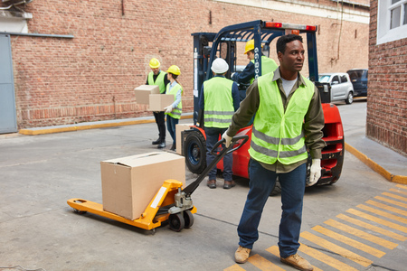 African worker in front of the logistics center with package on the pallet truck
