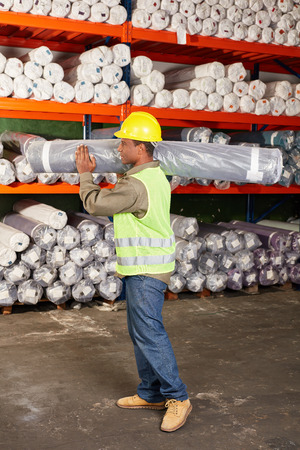 Worker in the carpet warehouse carries a carpet in the warehouse for shipment Banco de Imagens