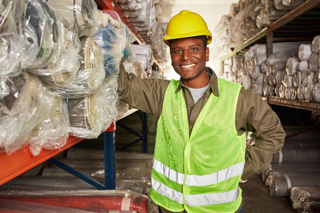 Young man as logistics apprentice to the warehouse specialist in the carpet warehouse is pleased