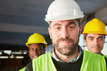 Man as a warehouse worker or warehouse specialist with colleagues in a logistics company