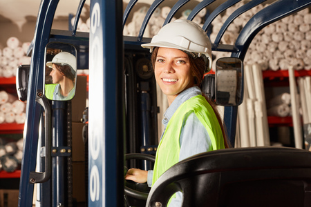 Young woman as a logistics trainee on the forklift in the warehouse of a company