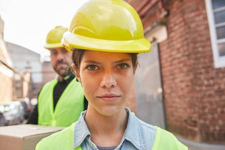 Young woman as apprentice in training in logistics profession with safety helmet