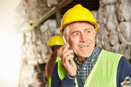 Senior as logistics Warehouse worker is on the phone talking to a mobile phone in the warehouse