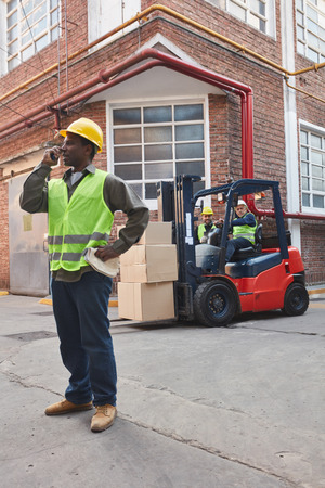 Worker with forklift and cargo in front of the depot of a logistics company Banco de Imagens
