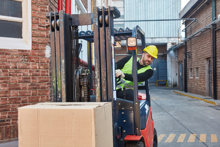 Logistics worker transports a package with the forklift for shipment