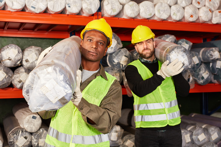 Two logistics workers of a freight forwarding company in the carpet warehouse transport delivery Banco de Imagens