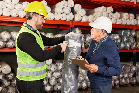 Order picker and a colleague with scanner and clipboard in the shipping warehouse Banco de Imagens