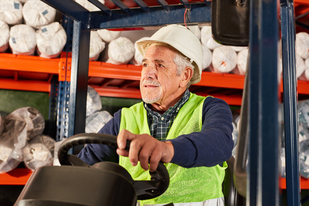 Senior as a driver on a forklift in a warehouse or logistics center