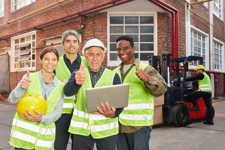 Successful logistics team with laptop PC with thumbs up in front of factory