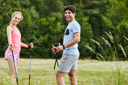 Young couple nordic walking together in summer