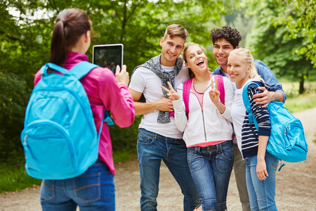 Hiking group of teenagers taking photograph with friends having fun
