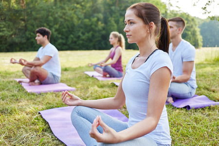 Woman meditating in yoga class in summer in nature