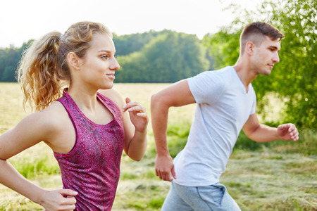 Young couple jogging at park in summer Banco de Imagens