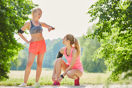 Two women are excited about running together in the park