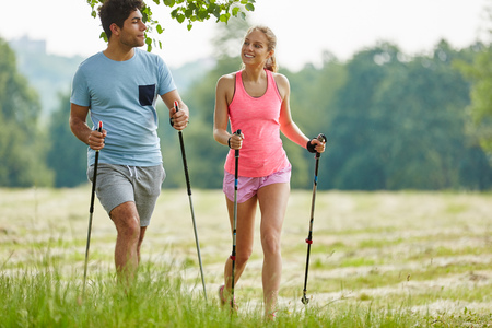 Man and woman nordic walking together in their leisure time