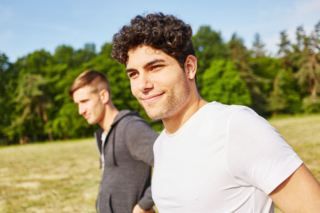 Young man as athlete doing sport with friend