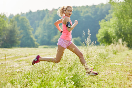 Young woman joggin with smartwatch in the nature during fitness training Banco de Imagens