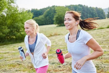 Due giovani amici che fanno jogging nel parco in estate Archivio Fotografico