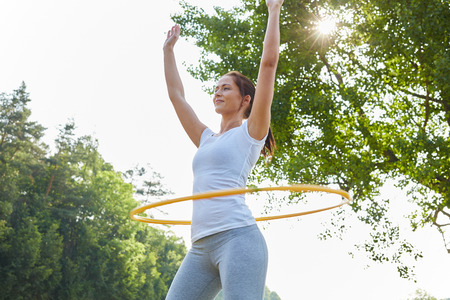 Woman exercices with hoop in fitness class in summer