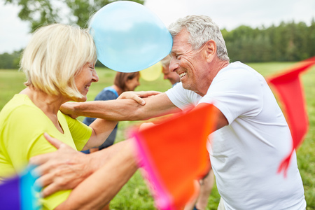 Seniors at a party play balloons to get to know each other Stockfoto