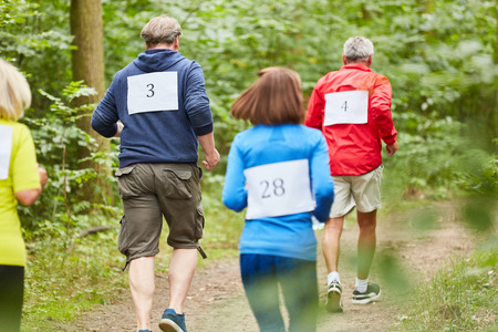 Vital seniors in running training for endurance together in nature 写真素材