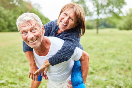 Happy senior man carries his wife piggyback on a meadow in summer