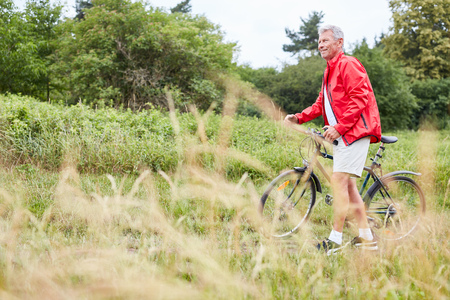 Sporty senior man trains his fitness by bike on a bike ride
