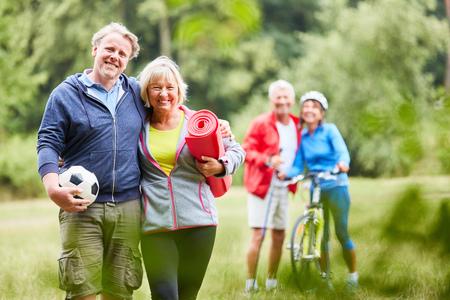 Vital pareja senior y amigos deportivos juntos en el verano en el parque